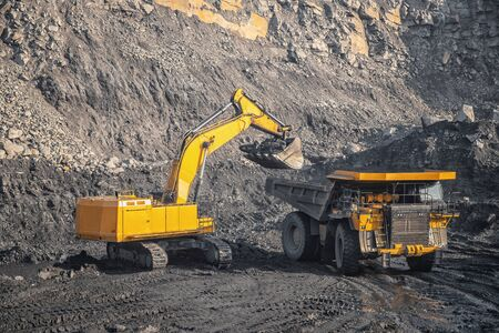 Hydraulic excavator loads coal into body of large yellow mining truck. Open pit mine industry for anthracite. 스톡 콘텐츠