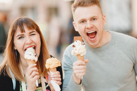 Cheerful couple man and girl friends in Rome eating Italy ice cream cones