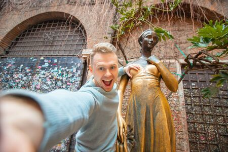Selfie photo of man holding statue of Juliet chest in Verona Italy, smiling and laughing. Travel concept
