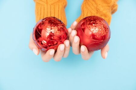 Beautiful female hands in warm knitted sweater holding New Year red balls to decorate Christmas tree