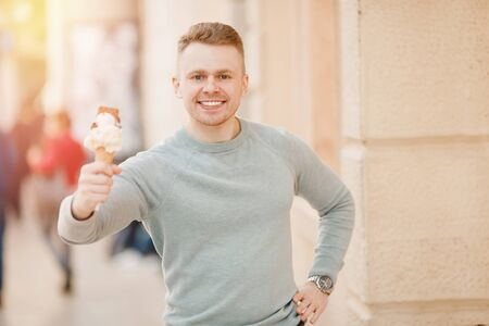 Happy male tourist holding italian ice cream in cone and smiling