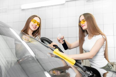 Two beautiful women worker washing windshield with sponge on car wash, window clean from dirt eco spray polishing