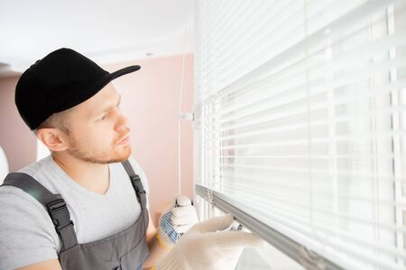 Construction worker man install blinds on plastic white upvc windows in house