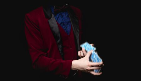 Focus with playing cards in hands of magician, black background close-up