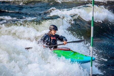 Whitewater kayaking, extreme sport rafting. Guy in kayak sails mountain river 写真素材