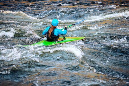 Girl in kayak sails mountain river. Whitewater kayaking, extreme sport rafting.