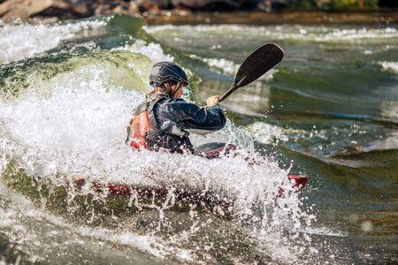 Whitewater kayaking, extreme sport rafting. Guy in kayak sails mountain river. Stock fotó