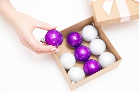 Girl opened box with New Year balls bubbles for Christmas tree, white background.