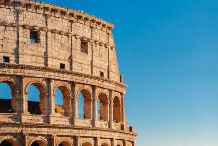 Colosseum or Coliseum ancient ruins background blue sky Rome, Italy