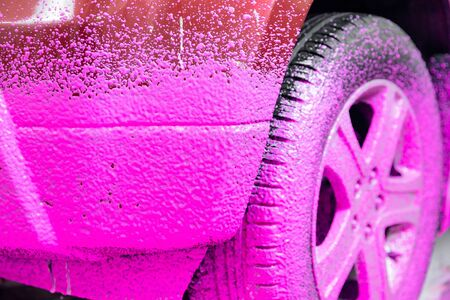 Car service detailing wash, pink foam to clean dirt with smell of cherries.