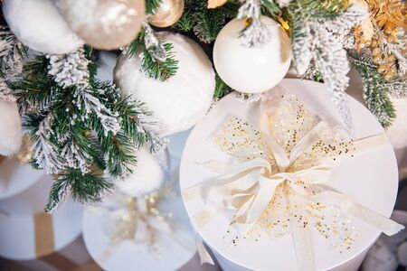 White boxes gifts on background of Christmas tree and fireplace, silver bow