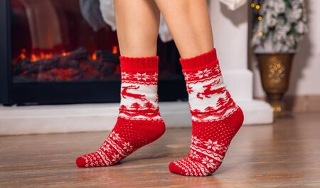 Legs young girl in red golf on socks walks after Christmas gifts on background of fireplace.