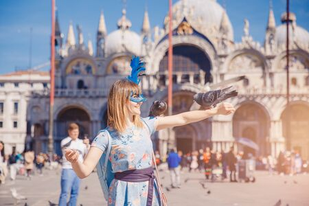 Portrait smiling young woman in Venice, Italy in Venetian mask feeds pigeons on St Mark Square. Concept travel