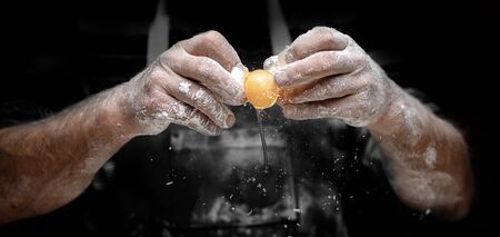Baker chef breaks yellow egg into fresh dough on kitchen table, black background.