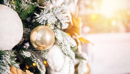 Decorated Christmas tree white and gold color, close-up of toys and decor, fireplace in background