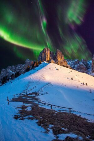 Aurora borealis northern lights on mountains forest night.