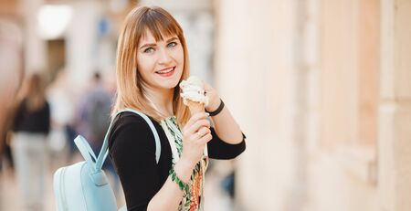 Beautiful girl tourist holds and eats Italian ice cream in cone and looks into frame