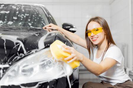 Worker beautiful woman cleaning auto black foam with yellow sponge. Car washing service