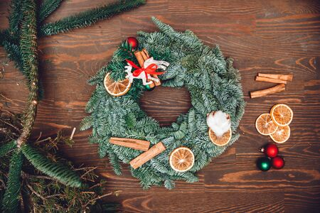 Christmas winter wreath decorations of dried oranges with cinnamon and deer with red ribbon on wooden background, top view