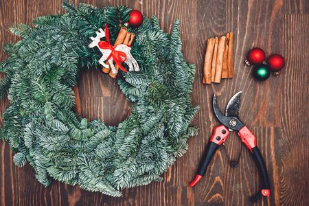 Top view florist making Christmas wreath on wooden table, flat lay tree branches secateurs, deer with red scarf