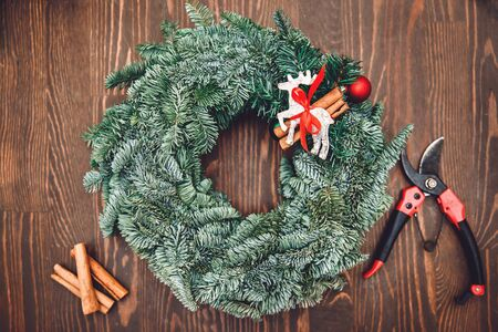 Top view florist making Christmas wreath on wooden table, flat lay tree branches secateurs, deer with red scarf.