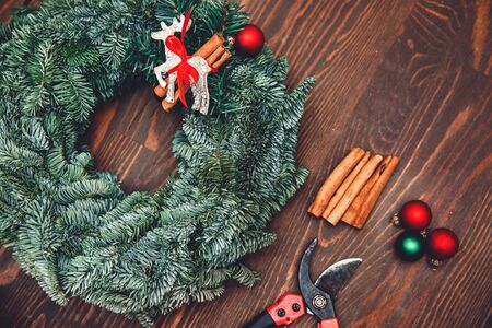 Christmas craft wreath on brown wooden table decorations DIY, top view. Banque d'images - 138471122