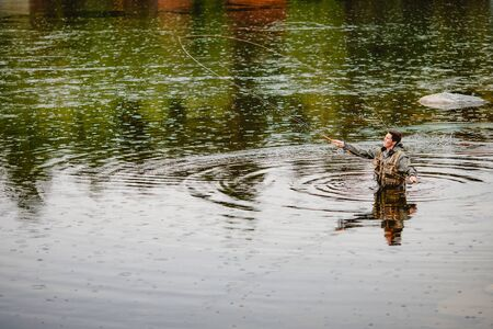 Fisherman using rod fly fishing in river morning standing in water.