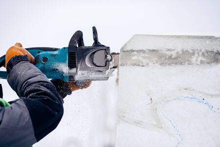 Ice sculpture carving man use electric chainsaw cut frozen winter.