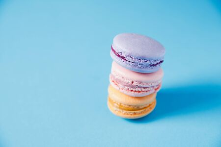 Colorful Cake macaron or macaroon on blue background, pastel color.
