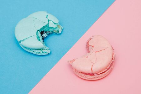 Bitten color macaroons on pink and blue background, top view.