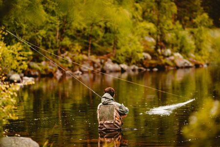 Fisherman using rod fly fishing in river morning standing in water