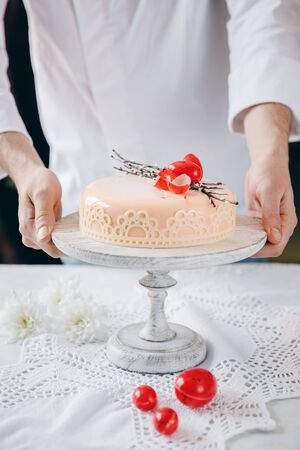 Male chef puts Easter cake kulich with chocolate eggs and willow on table