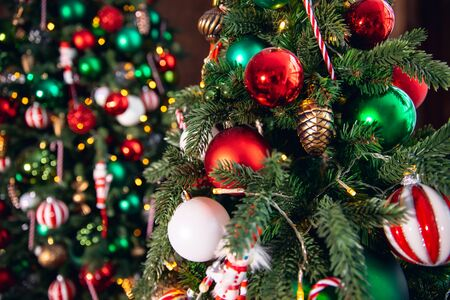 Decorated Christmas tree red and green color, close-up of toys and decor striped candy. Banco de Imagens