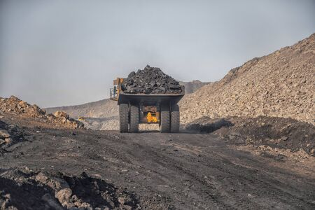 Big yellow mining truck laden anthracite moves open pit coal mine. Banco de Imagens