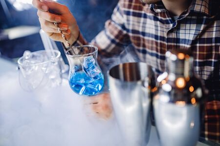 Barman mixes blue cocktail show with colorful alcoholic and smoke bar counter.