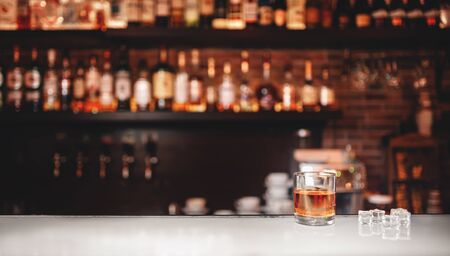 Glass of whiskey with ice stands on bar counter, dark brown background.