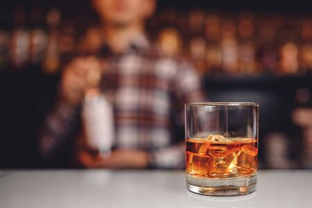 Barman holds out glass of whiskey with ice to male visitor. Concept rest in bar. Reklamní fotografie