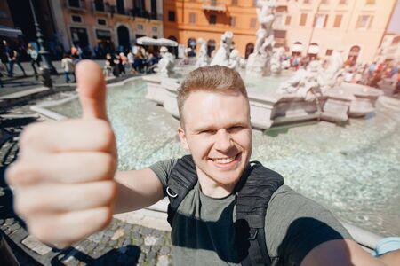 Happy man tourist taking selfie photo on background fountain Four rivers in Piazza Navona, Rome Italy Archivio Fotografico