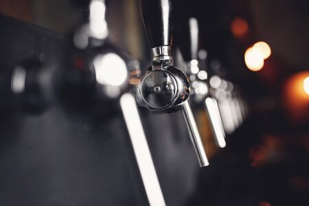 Beer craft steel taps raw in pub. Selective focus, dark background. Reklamní fotografie