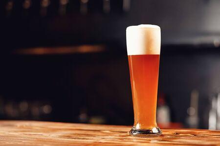Langes Glas frisches helles Bier mit Schaum auf Holzbartheke, dunkler Hintergrund Standard-Bild