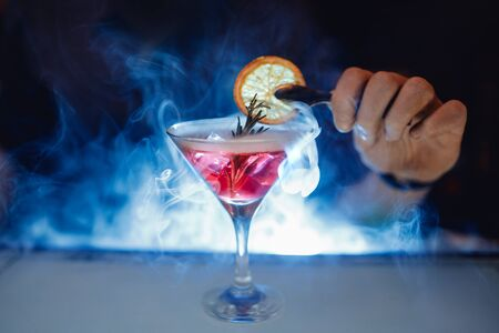 Barman make red alcoholic cocktail with smoke in glass, decorated with orange.