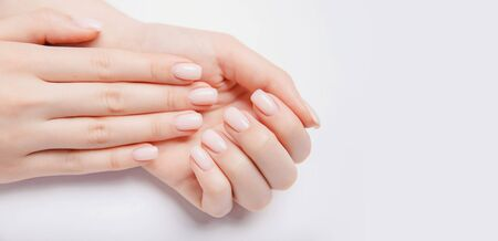 Stylish trendy nail young woman hands pink manicure on white background Stock Photo