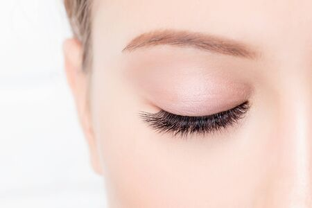 Closed female eye with beautiful makeup and long lashes on white background. Concept eyelashes extensions procedure.