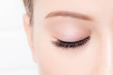 Occhio femminile chiuso con bel trucco e ciglia lunghe su sfondo bianco. Procedura di extension ciglia Concept.