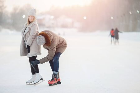 Man helps and shakes girl from snow after falling at ice rink in winter. Concept care and love of couple