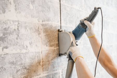 Builder man cutting electrical chase in concrete wall with groove machine diamond crown. Banco de Imagens