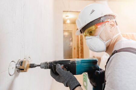 El martillo neumático del trabajador del constructor perfora el agujero en la pared de ladrillo de hormigón con corona de diamante para el cable eléctrico, el enchufe, el interruptor.