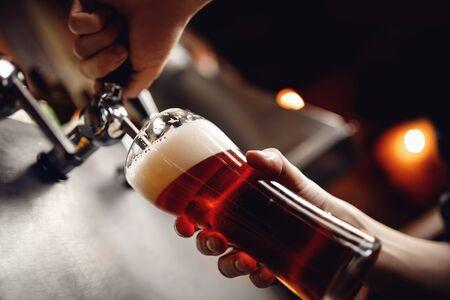 Il barista versa la birra artigianale dal rubinetto in vetro, sfondo scuro.