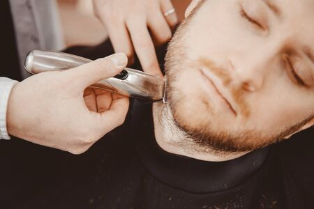 Close-up of barber shearing beard to man in barbershop electric razor Foto de archivo - 139415193