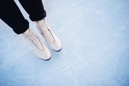 Woman standing on ice in white figure skates, snow flakes sunset. Top view.
